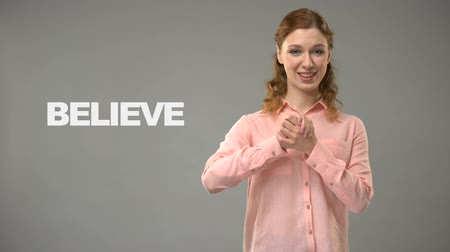 nonverbal : ASL teacher signing believe, text on background, communication for deaf, help