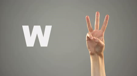 w : Letter W in sign language, hand on background, communication for deaf, lesson