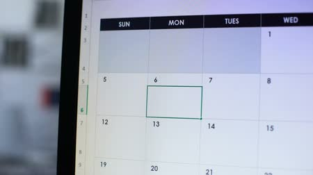 szervez : Person planning business meeting, scheduling date in calendar on computer, work