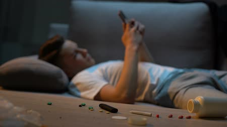 junkie : Teen boy lying on couch and scrolling phone, cigarette and drugs on foreground.