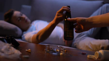 zararlı : Hand offering addicted young male bottle of beer, detrimental alcohol abuse
