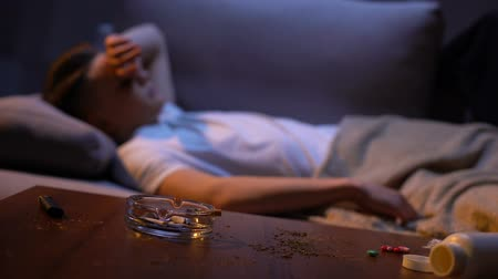 harmful habit : Teenager sleeping on sofa after smoking and taking drugs idle life harmful habit