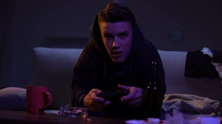 věk : Teen student playing video game and drinking beer, harmful alcohol addiction