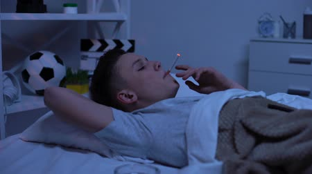 descuidado : Nicotine addicted teenager smoking in bed, harmful habit, risk of accident
