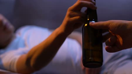 alkoholik : Male hand giving beer bottle to young teenager, home party, difficult age