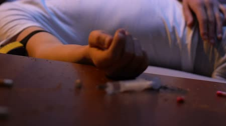 dose de : Syringe, cigarette butts and drug pills on table, man on background, overdose
