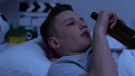 teen age : Teenager drinking beer, lying in bed, caught by parents, pretending to be cool Stock Footage