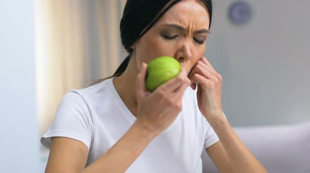 surroundings : Female freelancer looking through graphs, biting apple and feeling pain, carries Stock Footage