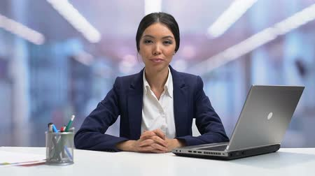 businesslady : Young self-confident businesslady looking to camera and smiling, slow-motion