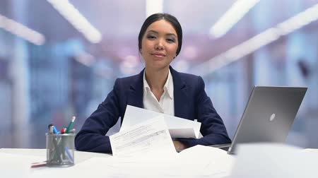businesslady : Papers falling around calm female office employee, high tolerance for stress
