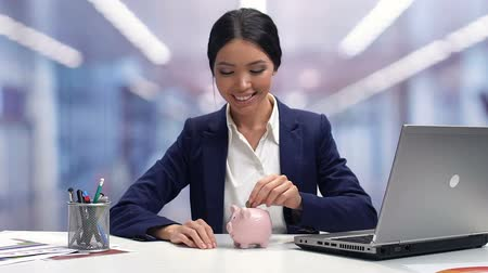 экономить : Smiling female in businesswear throwing coin in piggybank, savings for future
