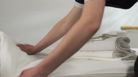 スイート : Female chambermaid preparing clean bed-linen, taking dirty towels from room