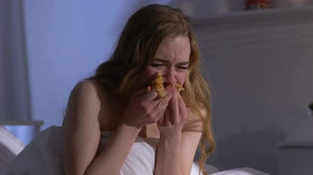 greedily : Crying woman greedily eating croissant in bed at night, weight problems, bulimia