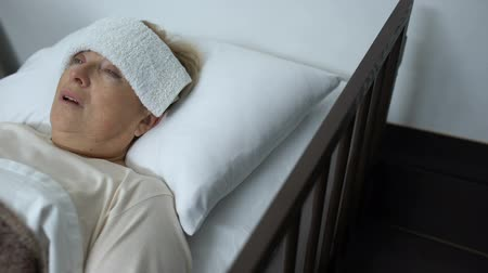 трепет : Sick mature woman lying in hospital bed with compress on forehead, fever or flu