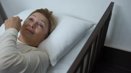 desesperado : Depressed old patient wiping tears lying in sickbed, volunteer supporting lady Stock Footage
