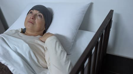 incurable : Depressed female patient suffering cancer lying in sickbed, incurable disease Stock Footage