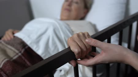 rehabilitasyon : Mature woman getting out of bed with help of nurse at first time after surgery