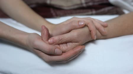 успокаивающий : Warm daughters hands stroking and calming down sick mother in bed, assistance