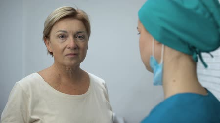 cardiologista : Mature woman listening to test results from doctor, suspicion of bad diagnosis