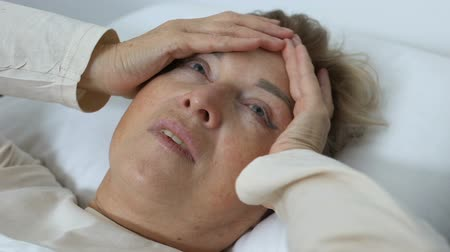 fraco : Old woman with migraine pain lying in bed, headache disorders, health problem