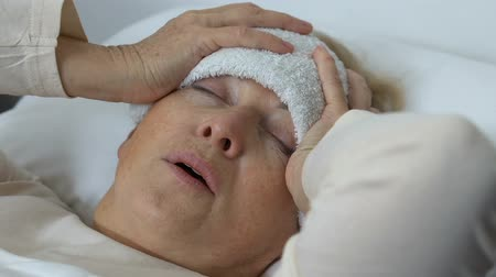 rehabilitasyon : Sick elderly lady holding head with wet towel on forehead, suffering from fever Stok Video