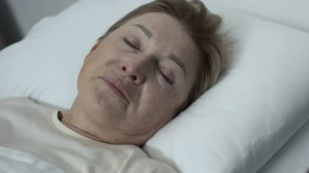desperate : Weak crying lady lying in bed and looking at camera, hospice center, despair Stock Footage