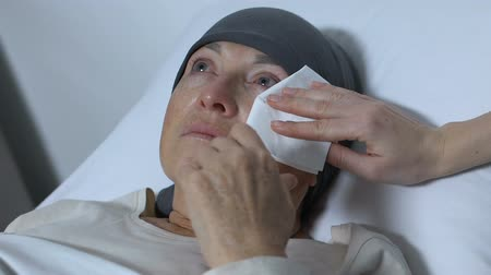 zayıf : Nurse wiping tears of old woman with cancer, rehabilitation after chemotherapy