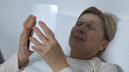 photograph : Crying senior woman lying in bed and looking at photo, remembering husband