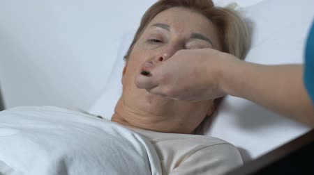 treating : Nurse treating old woman with syrup, female patient lying in hospital bed Stock Footage