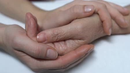 caregiver : Daughter and aged mother holding hands, family care and support, close-up