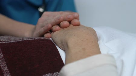 incurable : Nurse holding female patient hand lying in bed, suffering from incurable disease Stock Footage