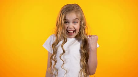 advert : Happy cute girl making yes gesture, surprised with good result, advertisement Stock Footage