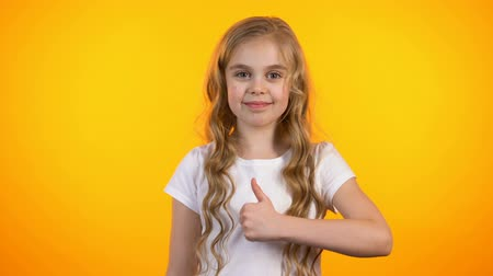 rekomendacja : Beautiful blond teenage girl making thumbs-up gesture and winking recommendation