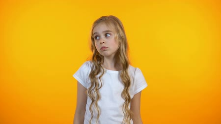 gesticulando : Confused kid shrugging on yellow background, lack of ideas, feeling uncertain