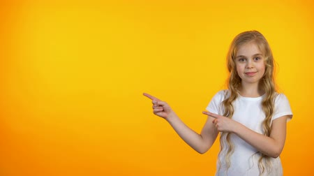 beautiful place : Satisfied adorable girl pointing at orange background, advertisement template