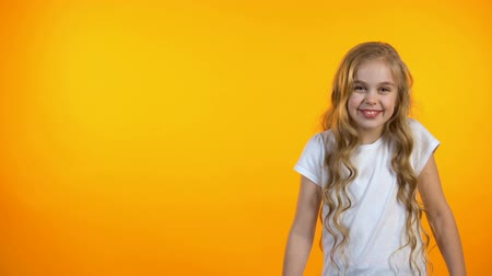 rekomendacja : Happy adorable girl laughing, standing on orange background, humor and jokes Wideo
