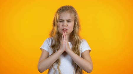 ilan : Cute schoolgirl praying, asking for dearest wish come true, anxious before exam Stok Video
