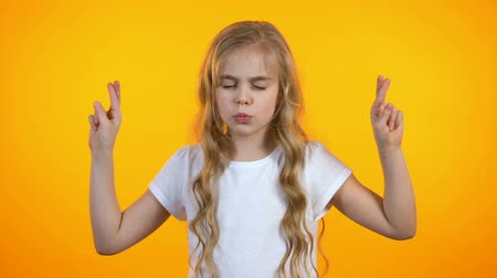 perguntando : Funny schoolgirl crossing fingers and praying, asking for dream birthday present