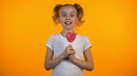 lolly : Funny schoolgirl licking heart-shaped lollipop, happy childhood, confectionery