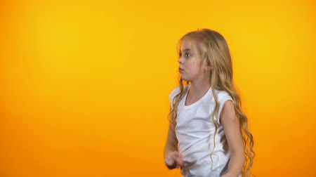 удовлетворенный : Funny preteen girl dancing, moving to music isolated on orange background Стоковые видеозаписи