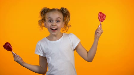 koketa : Adorable girl closing eyes with heart-shaped lollipops, smiling and having fun