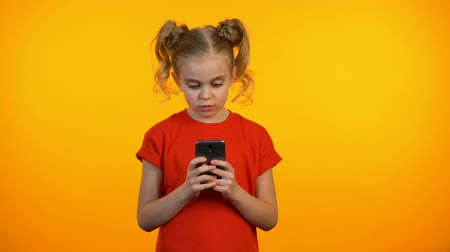 youngsters : Thoughtful preteen girl typing on smartphone, communicating with friends online Stock Footage
