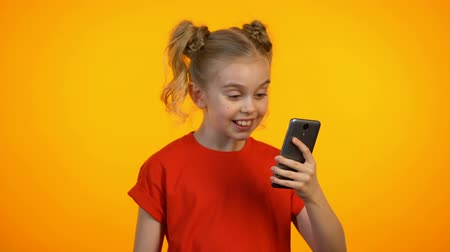 gesticulando : Funny little girl reading news in smartphone, smiling and showing thumbs-up