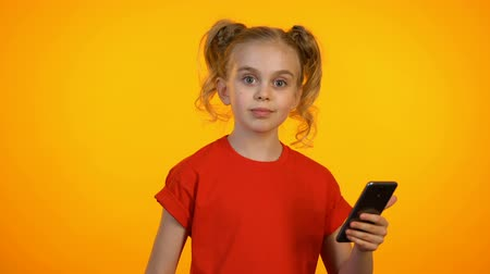 gesticulando : Cute girl showing typing and pointing at phone, winking and showing thumbs-up Vídeos