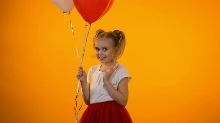 кампания : Funny schoolgirl holding balloons, smiling and making air kisses, first love