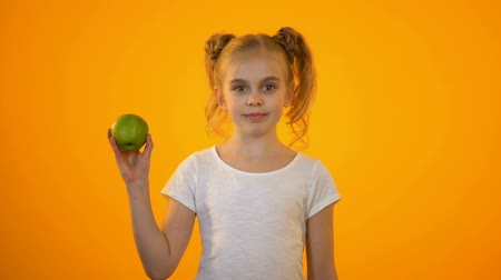 advert : Cute teenage girl showing fresh green apple, healthy nutrition, organic food