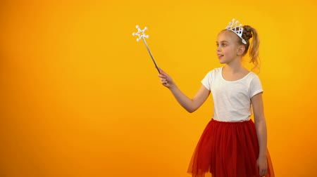 předstírat : Cute girl in fairy outfit looking to camera, little princess playing magic wand