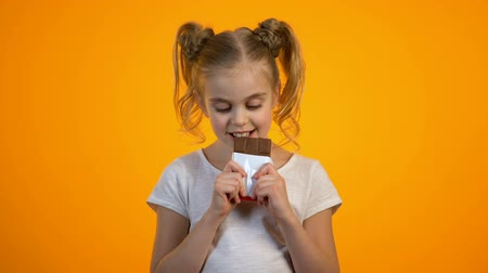gesticulando : Happy smiling preteen girl eating delicious chocolate, enjoying sweet taste