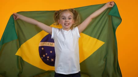 brasil : Adorable preteen girl jumping with brazilian flag cheering for favorite team Stock Footage