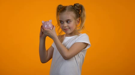 alfabetização : Adorable girl shaking piggybank, financial literacy, deposit for future, savings